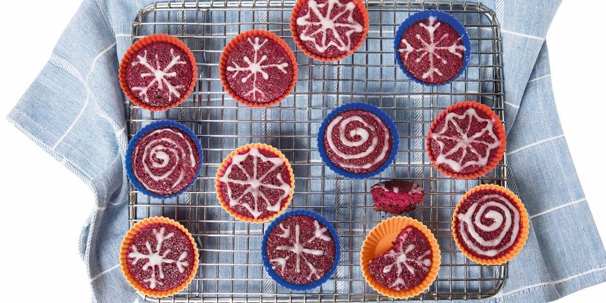 Fotografia em tons de azul e vermelho em um fundo branco com um pano de prato azul jeans com listras brancas, um suporte de gradil com vários cupcakes coloridos de beterraba.