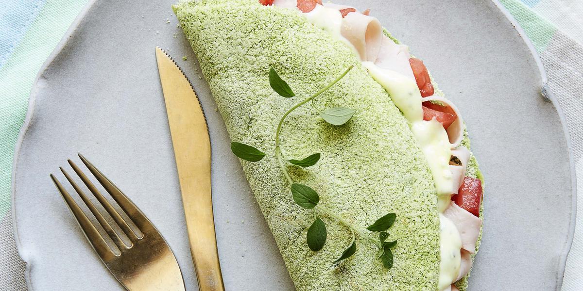 Fotografia em tons de verde em uma mesa de madeira com um pano listrado colorido em tons claro, um prato lilás redondo raso com uma tapioca verde de espinafre em cima dele.