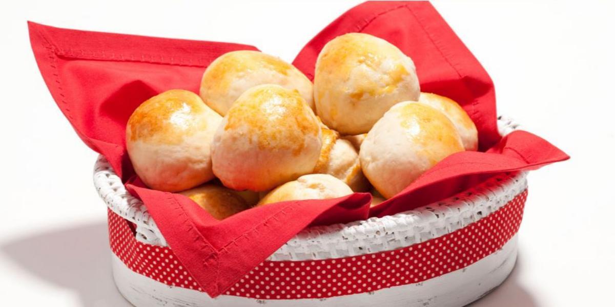 Fotografia em tons de branco e vermelho de uma bancada branca, sobre ela uma cesta branca e vermelha com um paninho vermelho com pães.