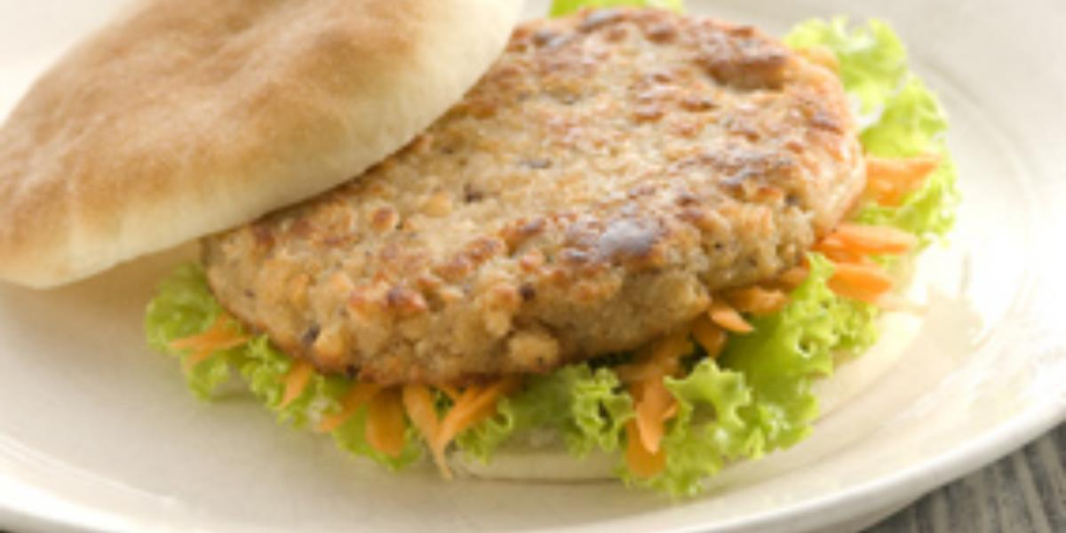 Fotografia de um prato branco com jogo americano de palha abaixo. No prato pão, hambúrguer, alface e cenoura.