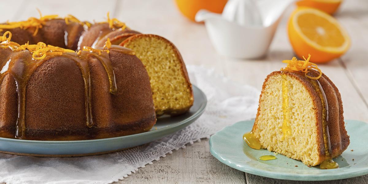 Foto com um bolo redondo de laranja, decorado com calda e raspas de laranja e uma fatia deste mesmo bolo num prato azul do lado direito da foto
