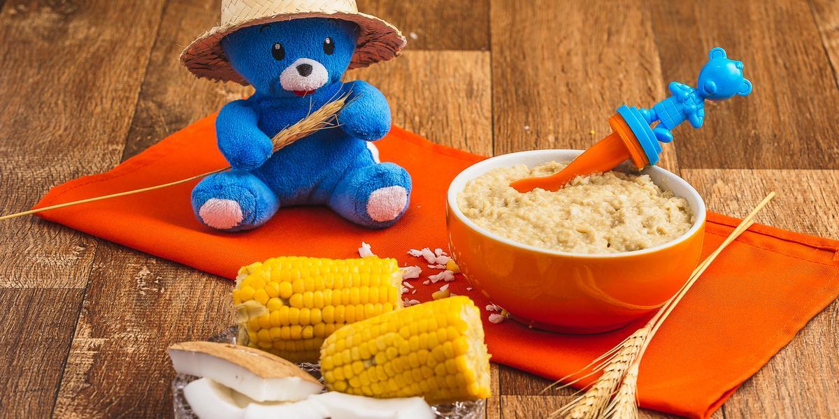 Fotografia em tons de laranja e azul de uma bancada de madeira com um paninho laranja e um potinho com uma papinha dentro. A frente uma espiga de milho ao meio, pedaços de coco e atrás um ursinho de pelúcia azul com um chapéu de palha.