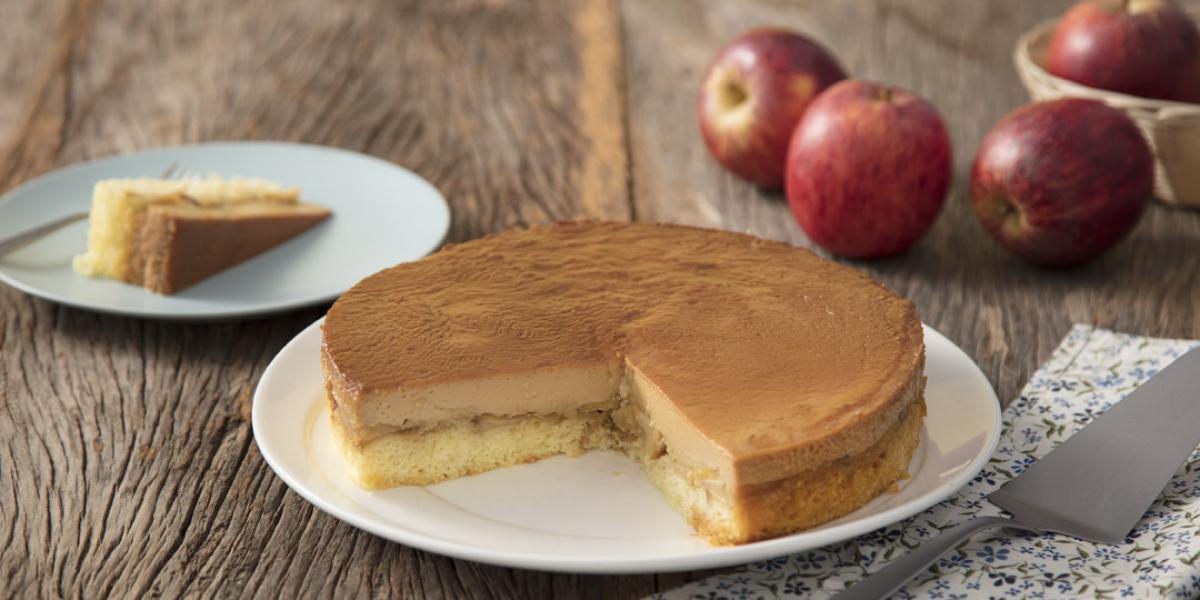 foto em tons de marrom e vermelho de uma bancada marrom vista de frente, contém um prato branco redondo com um bolo com uma fatia retirada. Ao lado um prato redondo com a fatia e ao fundo maçãs