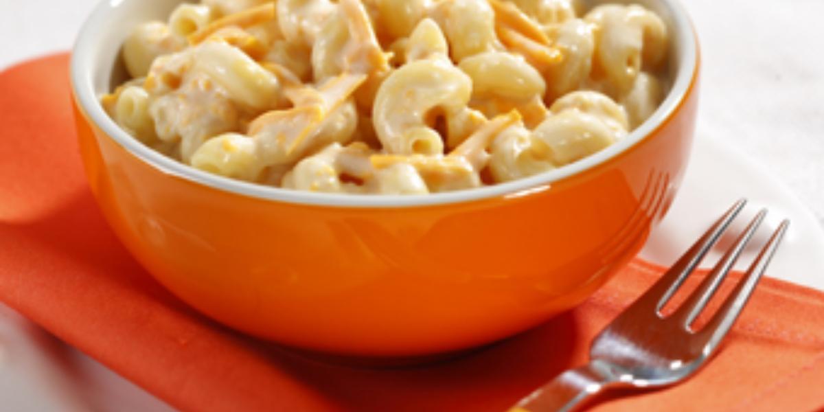 Fotografia em tons de laranja e branco, um prato redondo branco com um paninho laranja dobrado em cima, um garfo com cabo amarelo e um potinho laranja com o macarrão cremoso dentro.
