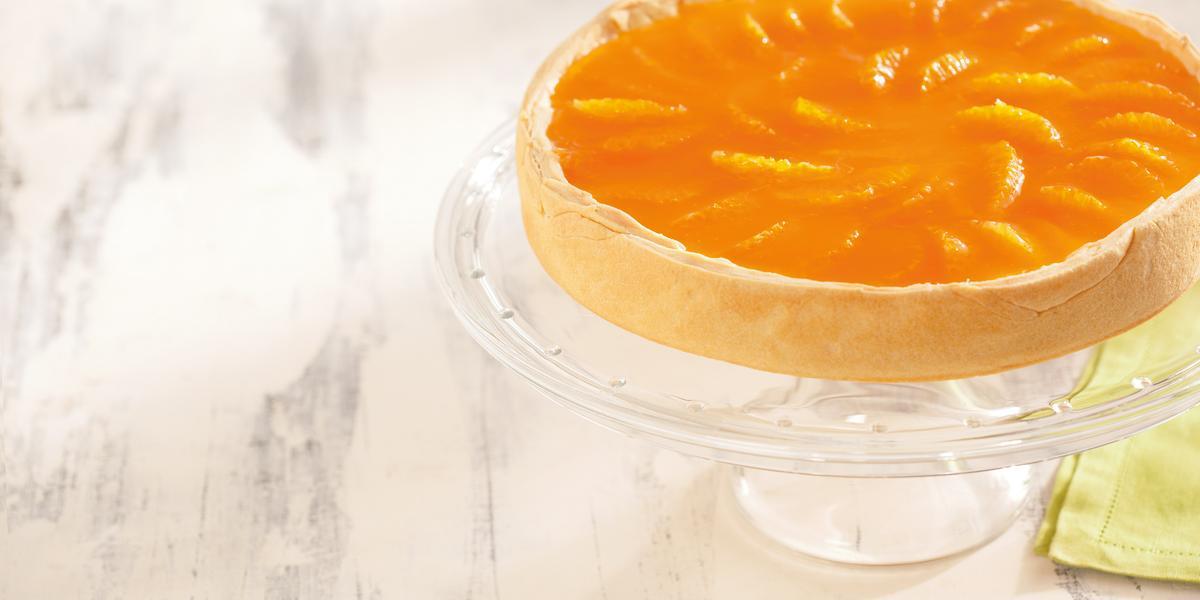 foto em tons de branco e laranja de uma bancada branca vista de cima. Contém um suporte para servir sobremesas transparente com uma torta com cobertura de tangerina por cima.