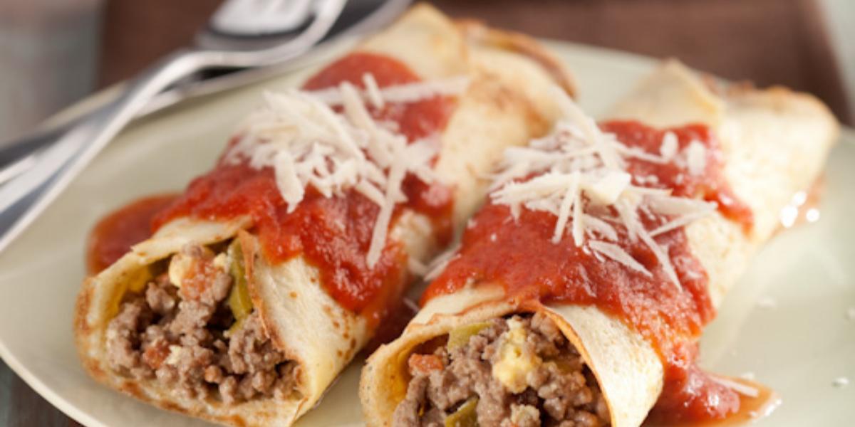 Foto de duas panquecas de carne moída cobertas com molho de tomate e queijo em um prato branco em cima de um pano marrom