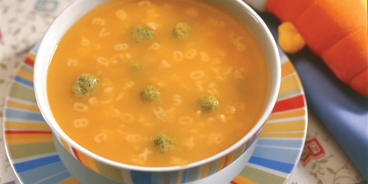 Fotografia em tons de laranja em uma mesa com uma toalha de folhas, um prato raso colorido, um prato fundo redondo colorido com a sopa divertida com bolinhas de espinafre.
