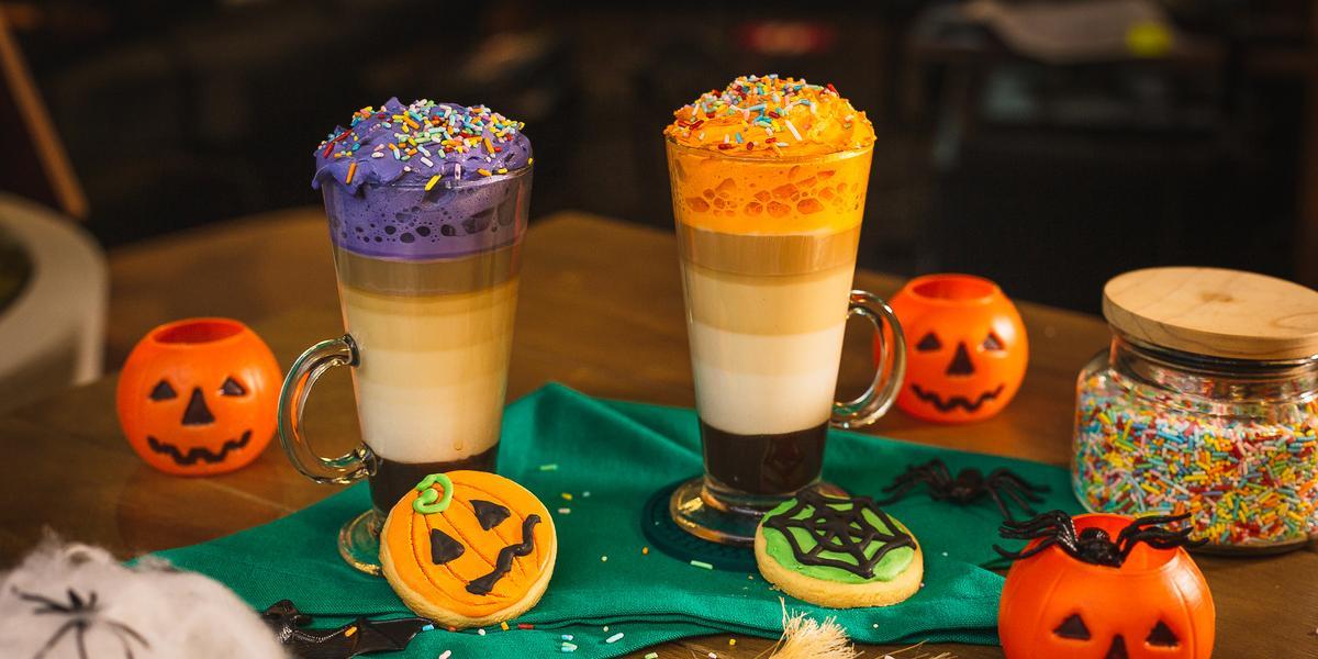 Fotografia em tons de laranja de uma mesa de madeira, duas bebidas, uma decorada com chantilly roxo e uma decorada com chantilly laranja. Em volta biscoitos decorados de abóbora, teia de aranha e elementos de halloween.