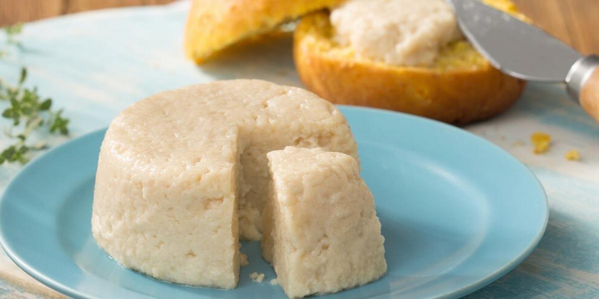 Fotografia em tons de azul e branco de uma bancada azul claro vista de frente, um prato redondo e azul contém um queijo redondo com uma fatia retirada. Ao fundo um pão redondo cortado ao meio e uma espátula com creme colocando em uma das fatias do pão.
