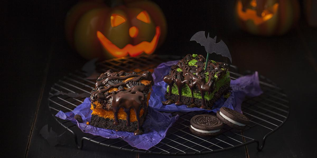 Fotografia em tons de roxo e laranja em uma bancada preta com desenhos de morcegos e abóboras desenhadas ao fundo. Ao centro, um suporte de grelha preto com os pedaços de bolos de chocolate com Negresco em cima.