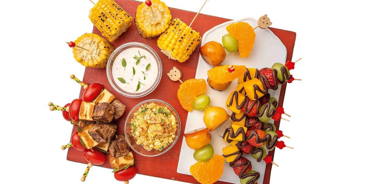 Em uma tábua vermelha contém diversos espetinhos de frutas como manga, morango e uva com cobertura de chocolate. Ao lado espetinhos de carne e milho e ao centro dois potes, um com molho e o outro com farofa
