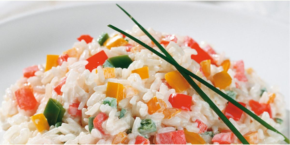 Fotografia em tons de branco e multicoloridos, porcelana branca com porção de arroz com legumes picados e decorados com duas folhas de cebolinha-verde, dois guardanapos brancos ao lado, tudo sobre bancada branca.