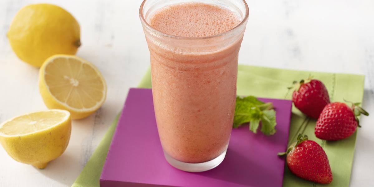 Fotografia em tons de branco, roxo e verde de uma bancada de madeira branca e um paninho verde, sore ele um apoio de copo quadrado roxo com um copo de vidro com o suco de morango. Ao lado três morangos e dois limões.