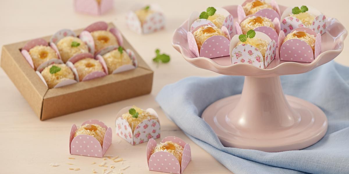Fotografia em tons de rosa em uma bancada de madeira rosa com um pano azul, um suporte para bolo rosa com alguns brigadeiros brancos com geleia de maracujá em forminhas rosas. Ao fundo, uma caixinha bege com mais brigadeiros brancos.