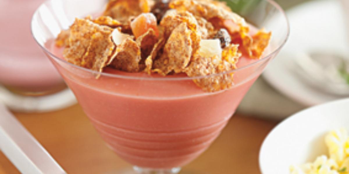 uma taça transparente contém creme de goiaba com cereal por cima