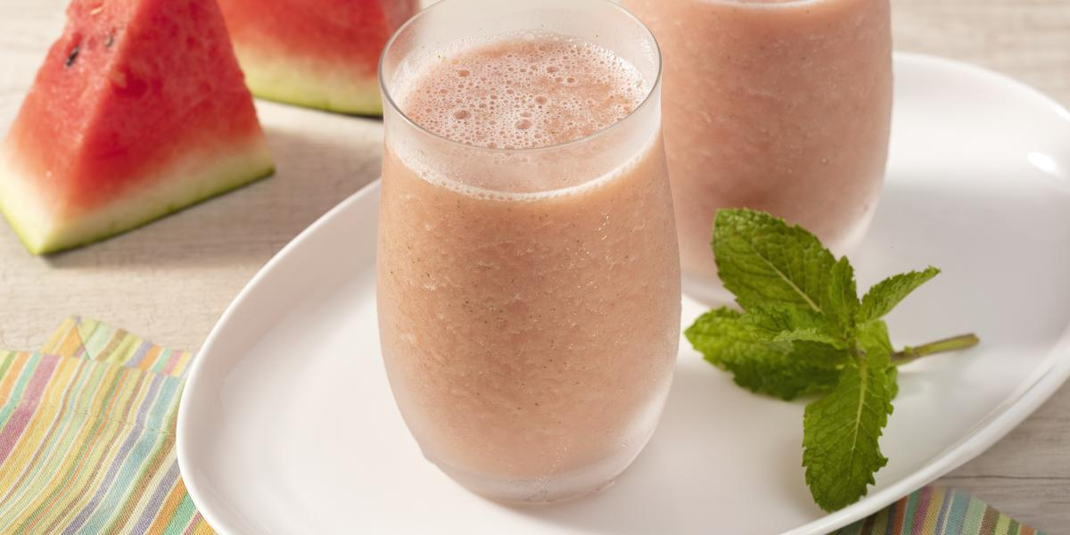 Fotografia em tons avermelhados, com pedaços de melancia cortados de forma triangular, prato oval branco com folhas de hortelã e dois copos de vidro com a bebida de melancia..