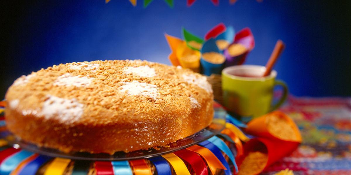 Foto de um bolo redondo em cima de um prato com fitas de cetim decorando ele e bandeirolas de festa junina ao fundo