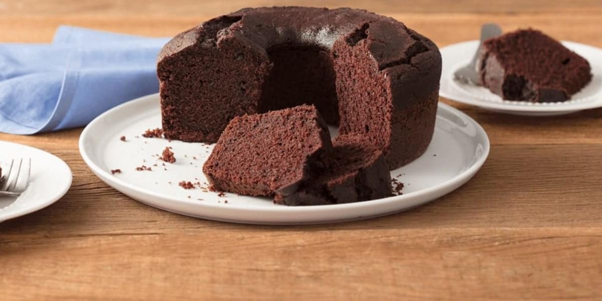 Fotografia em tons de marrom e branco de uma bancada de madeira clara com um paninho azul claro e um prato branco redondo com o bolo de chocolate. Aos lados dois pratos brancos pequenos com fatias de bolo de chocolate e um garfo.