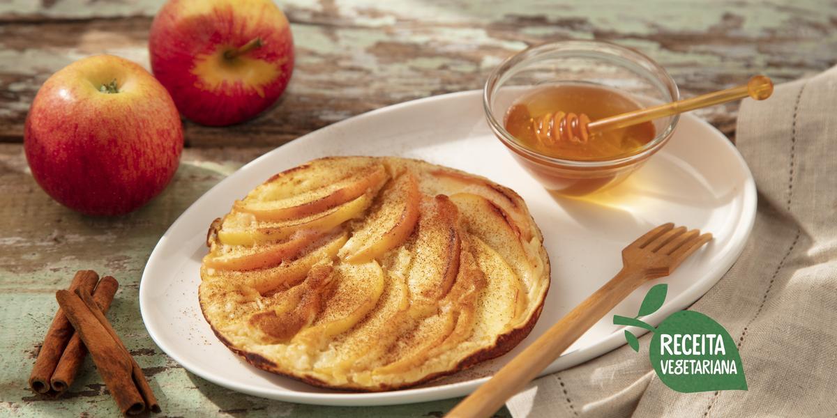 Fotografia em tons de marrom, branco e vermelho de uma bancada de madeira com um paninho branco, sobre ele um prato oval branco com uma panqueca, um garfo de madeira e um pote de vidro com mel. Ao fundo duas maçãs e ao lado dois paus de canela.
