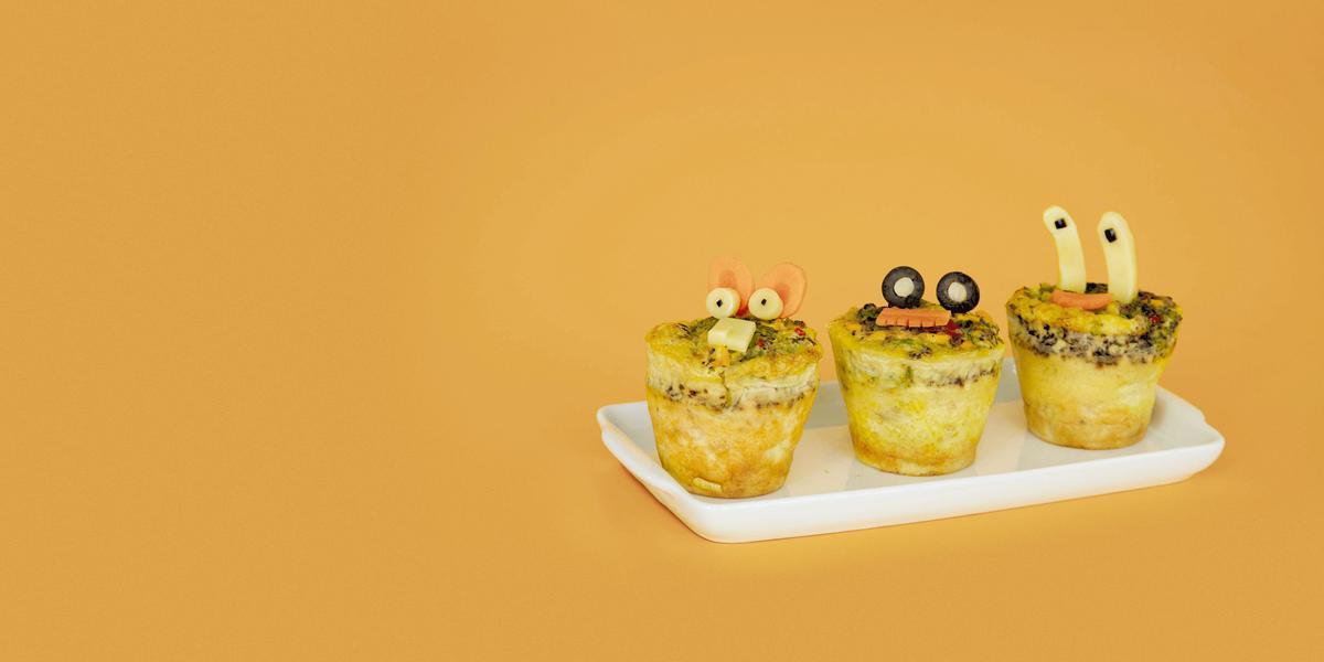 Fotografia em tons de amarelo em uma mesa e fundo amarelo escuro, um recipiente branco retangular e três mini muffins de omelete com desenhos infantis.