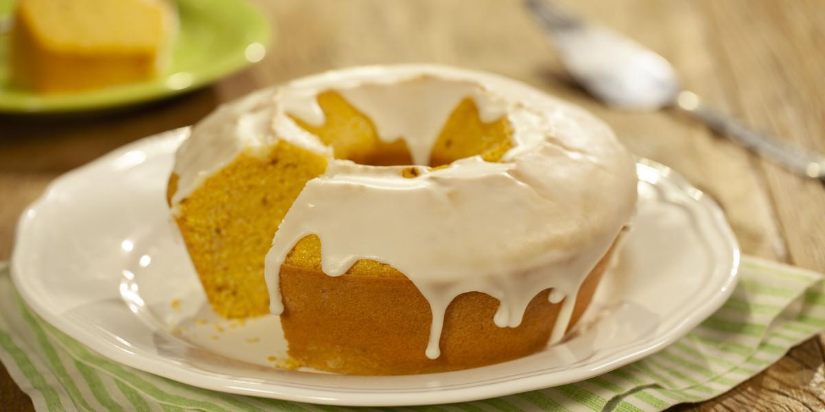Fotografia em tons de marrom, verde e branco de uma bancada de madeira com um paninho verde, sobre ele um prato redondo branco com um bolo de fubá. Ao fundo uma espátula e um prato redondo verde com uma fatia de bolo.