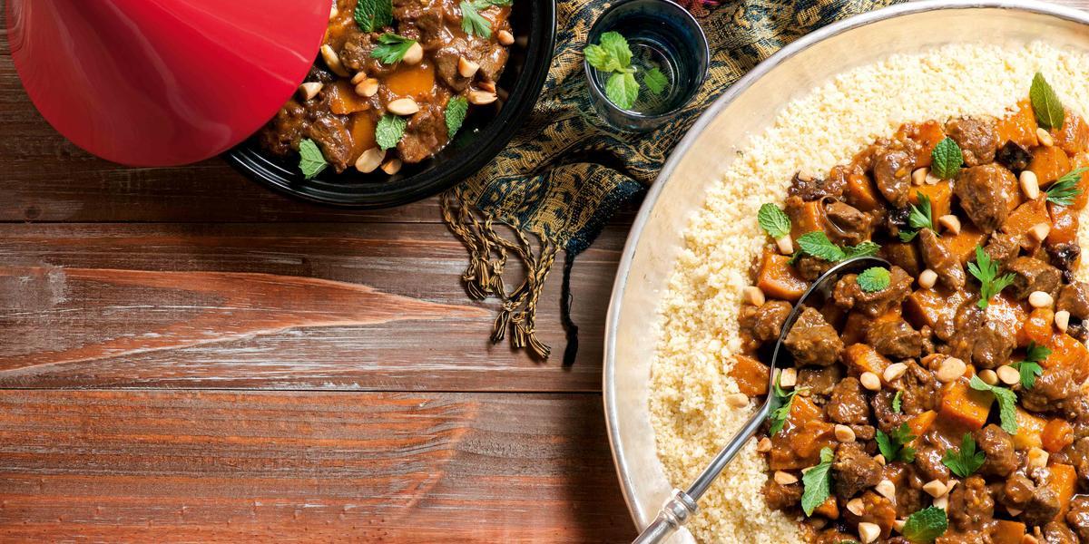 Fotografia em tons de vermelho em uma bancada de madeira escura, um prato grande redondo com o cordeiro com cuscuz dentro dele. Ao lado, um bowl apenas com a carne e potinhos com especiarias.