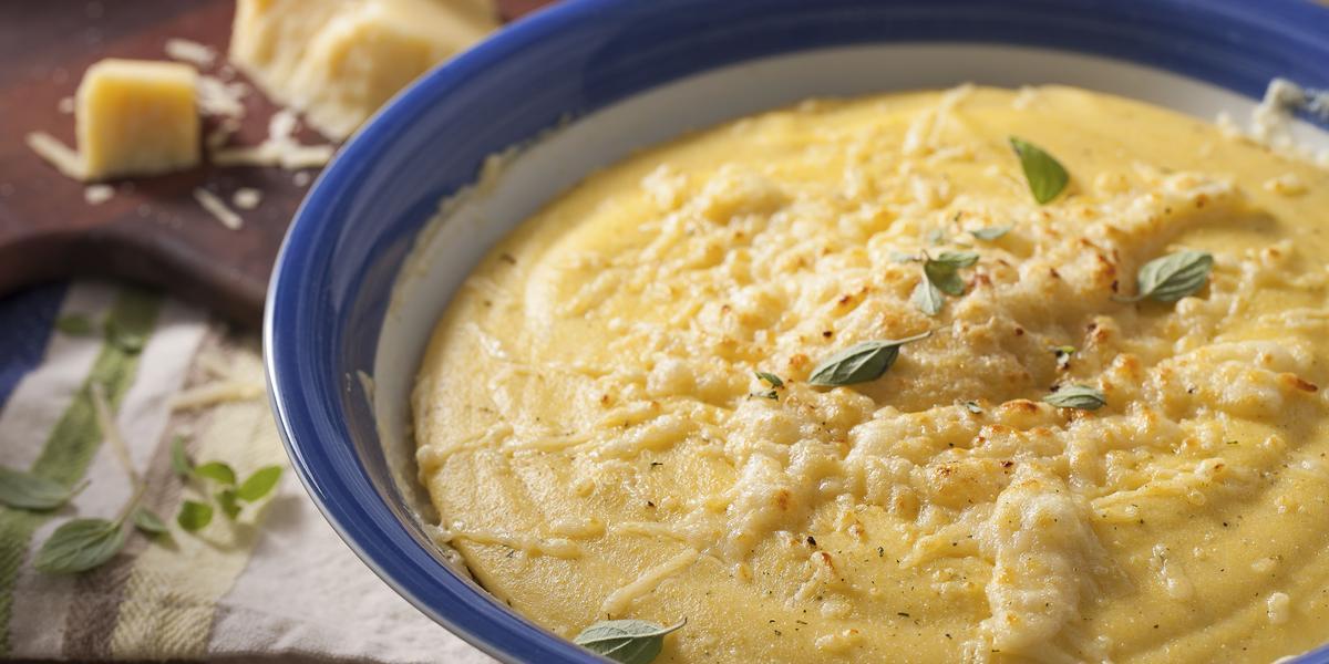 Fotografia em tons de marrom e azul de uma bancada marrom com um paninho branco, sobre ele um recipiente redondo branco e azul com polenta. Ao fundo uma tábua com queijo parmesão.