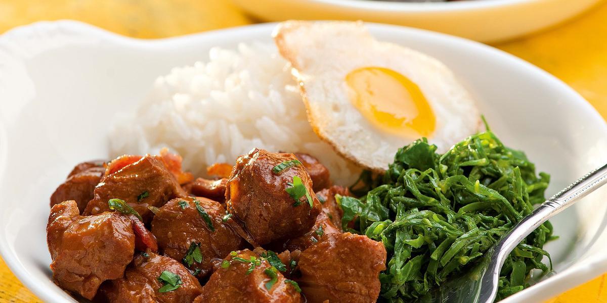 fotografia vista de frente, contém dois recipiente branco e redondo e ambos contém: arroz, couve, pedaços de carne e ovo com um garfo para servir