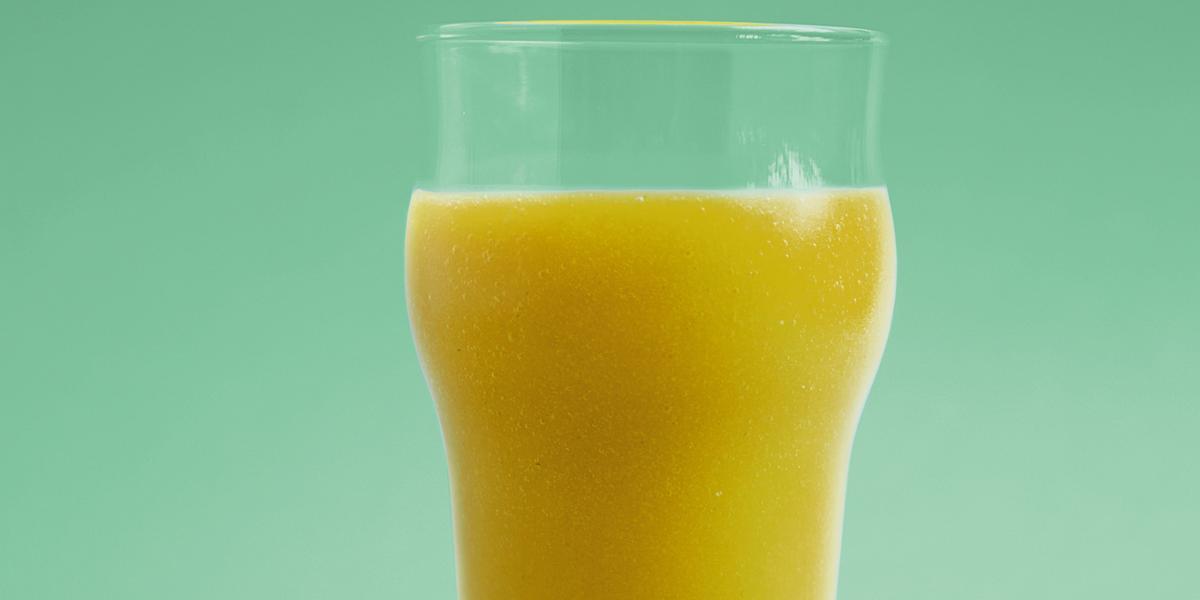 Fotografia em tons de verde em um fundo e bancada verde com um copo de vidro e o suco de manga, limão-siciliano e erva-cidreira dentro dele.