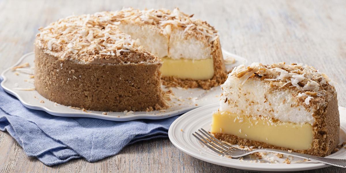 Fotografia em tons de marrom e azul de uma bancada de madeira com um paninho azul, sobre ele um prato branco com uma torta de coco. Ao lado um prato pequeno redondo com uma fatia da torta e um garfo.