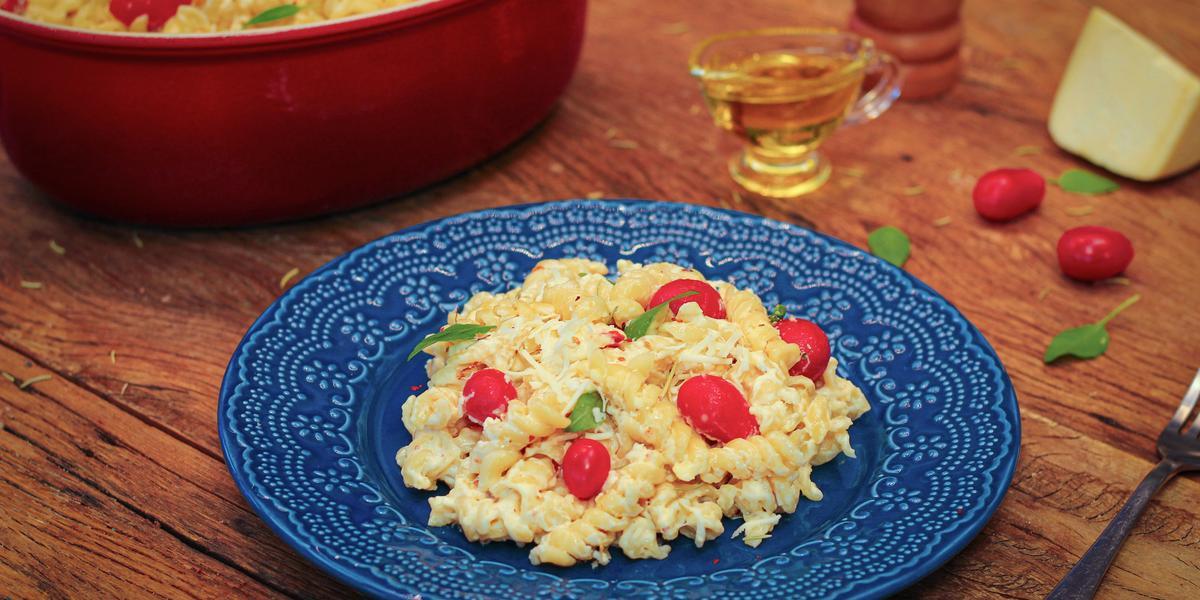 Fotografia em tons de marrom e azul de uma bancada de madeira com um prato azul, sobre ele macarrão com queijo e tomatinhos. Ao lado dois tomatinhos, um pedaço de queijo, um recipiente com azeite e um recipiente redondo vermelho com o macarrão.