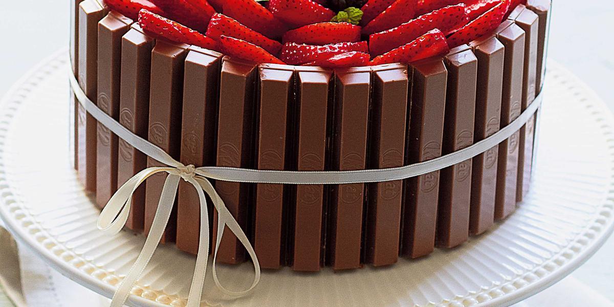 Fotografia em tons de branco de uma bancada branca com um paninho branco, um suporte para bolo branco e um bolo de Kitkat com frutas vermelhas. Ao lado um recipiente redondo branco com frutas vermelhas.