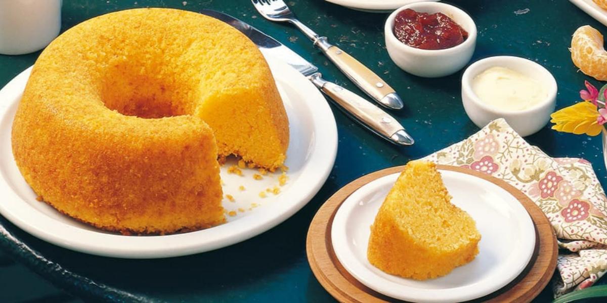 Fotografia em tons de amarelo, branco e azul escuro de uma bancada azul escura vista de cima. Um prato redondo e branco com o bolo faltando uma fatia e ao lado um prato redondo branco com uma fatia de bolo.