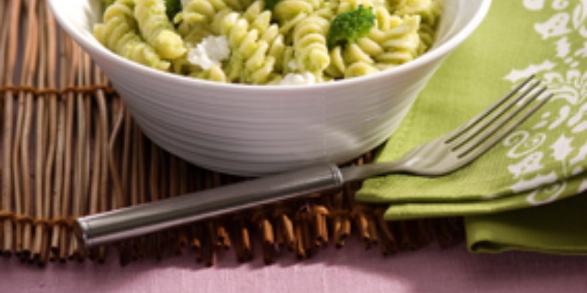 Fotografia em tons de verde em uma mesa de madeira com uma toalha rosa e um jogo americano de palha marrom.  Ao centro, um prato branco fundo redondo com o macarrão tipo parafuso com o molho pesto de brócolis e ao lado um guardanapo de pano verde.