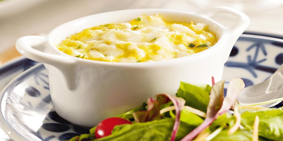 Fotografia em tons de verde e azul em uma bancada de madeira branca, um prato branco com detalhes azuis ao centro e salada verde em cima dele, com um potinho branco e a brandade de bacalhau dentro dele.