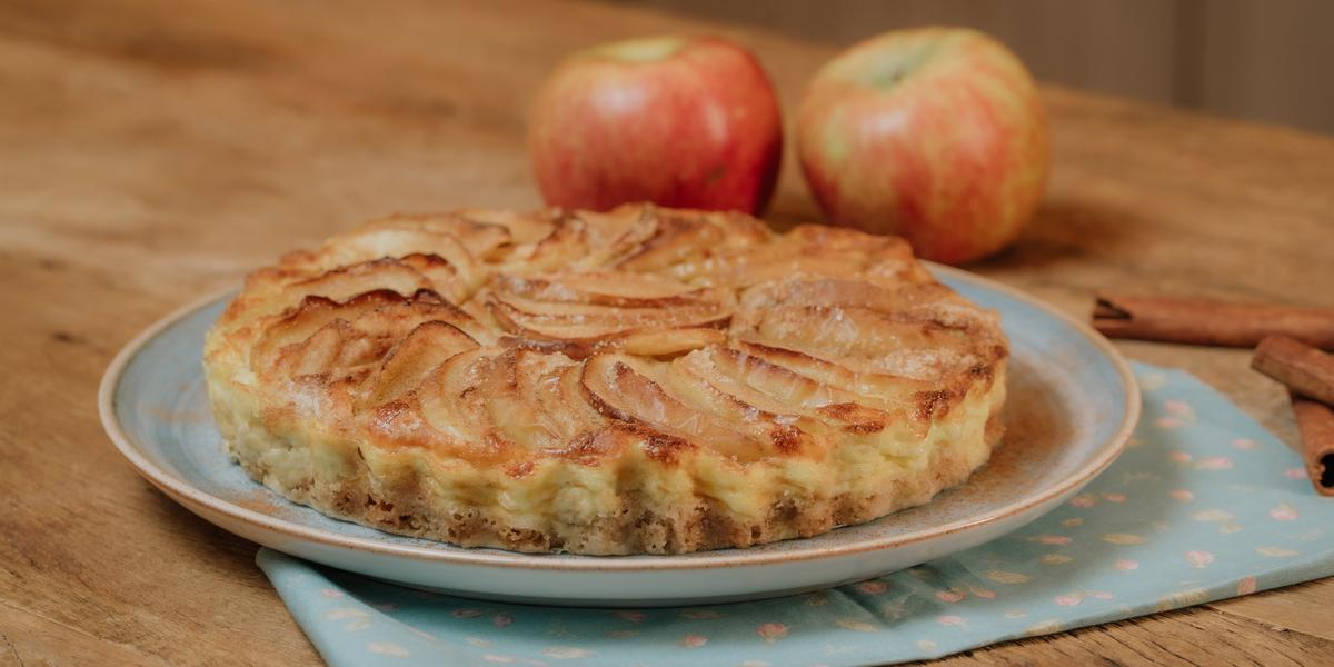 Fotografia em tons de marrom e azul de uma bancada de madeira com um paninho azul sobre ele um prato azul com uma torta de maçã. Ao fundo duas maçãs e paus de canela.