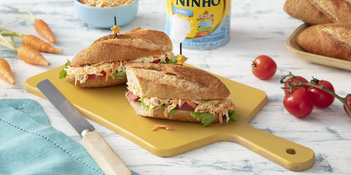 Fotografia em tons de azul e amarelo de uma banca, ao centro uma tábua de corte amarela, duas fatias de sanduíche recheado com alface, frango e cenoura ralada e ao fundo uma lata de NINHO Levinho, tomates e pães.