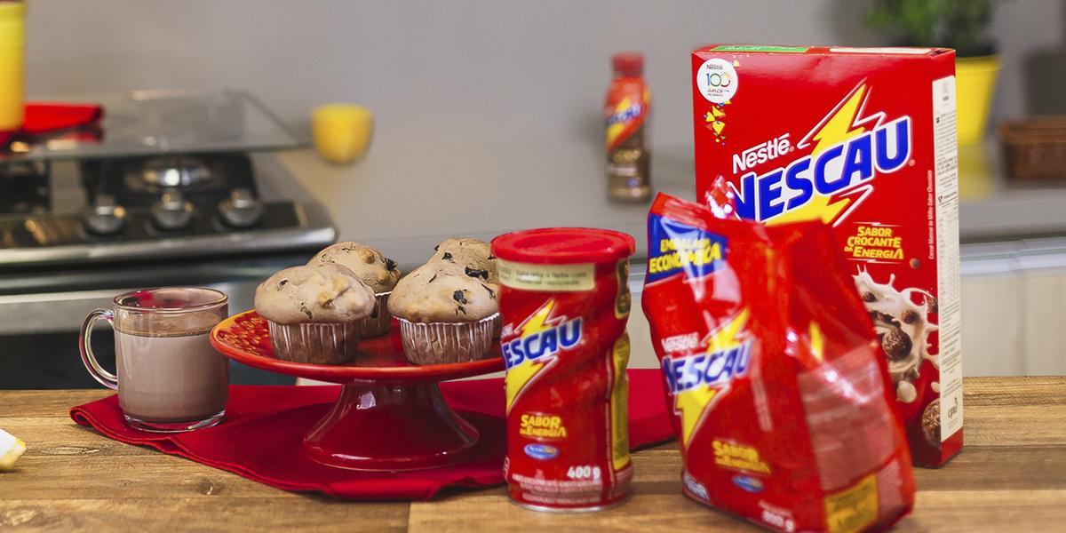 Foto vista de frente para um bancada com produtos Nescau à direita, mais ao centro um prato vermelho alta com quatro Muffins Crocantes de Nescau e à esquerda uma caneca com leite e Nescau.