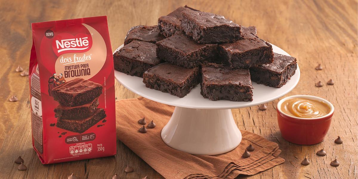 Fotografia em tons de marrom e vermelho de uma bancada de madeira com um paninho, sobre ele um prato branco com pedaços de brownie. Ao lado um potinho com Moça de colher doce de leite e um pacote de brownie dois frades.