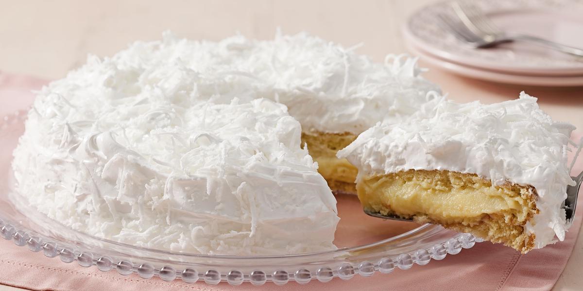 Fotografia de um bolo coberto com marshmallow branco e raspada de coco em cima. Dentro do bolo creme e massa brancos. O prato está em cima de um guardanapo de papel rosa claro.