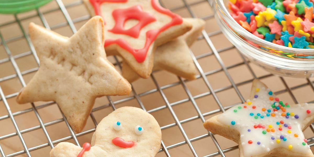 Fotografia de biscoitos decorados de natal em formato de boneco, estrela e presentes, nas cores vermelho, verde e branco, decorados com confeitos das mesmas cores.
