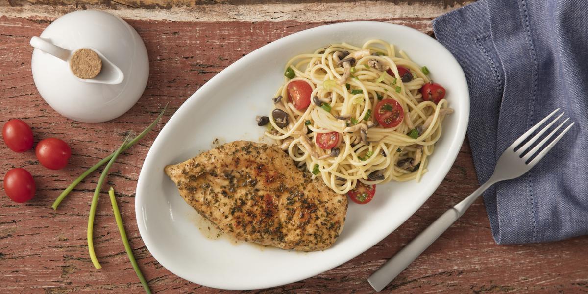 Fotografia em tons de azul e vermelho em uma bancada de madeira com um pano azul ao lado, um recipiente oval branco fundo com o macarrão com cogumelos e tomates e ao lado um filé de frango.