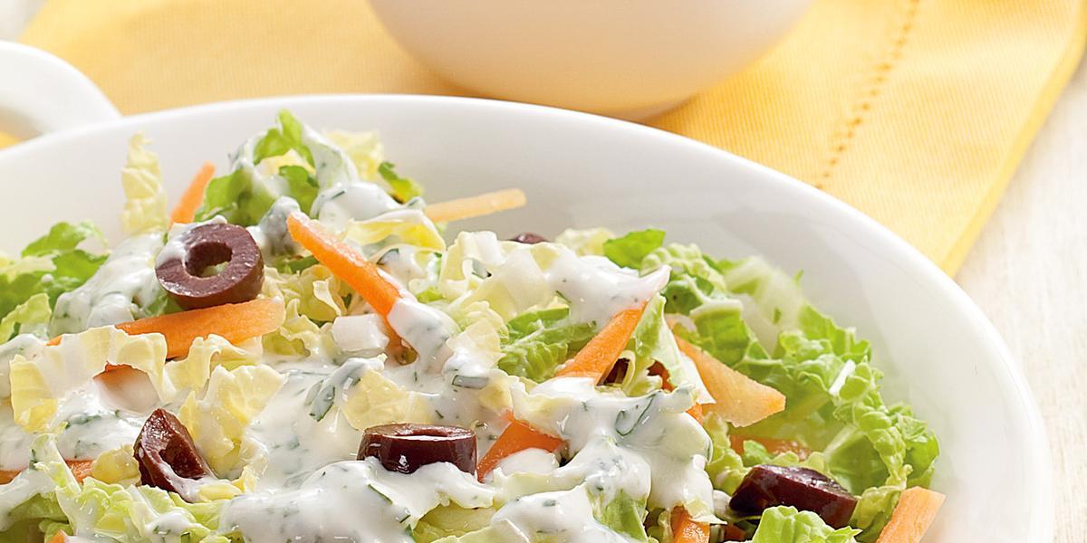 Fotografia em tons de tons de branco, amarelo e verde, saladeira com folhas verdes, azeitona, cenoura e molho de iogurte sobre guardanapo amarelo, ao lado potinho com molho de iogurte e folhas de hortelã, tudo sobre bancada em tom pastel.