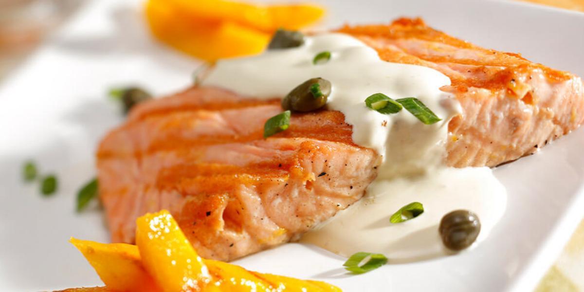 uma travessa branca contém um salmão com creme branco por cima e ao lado fatias de manga.