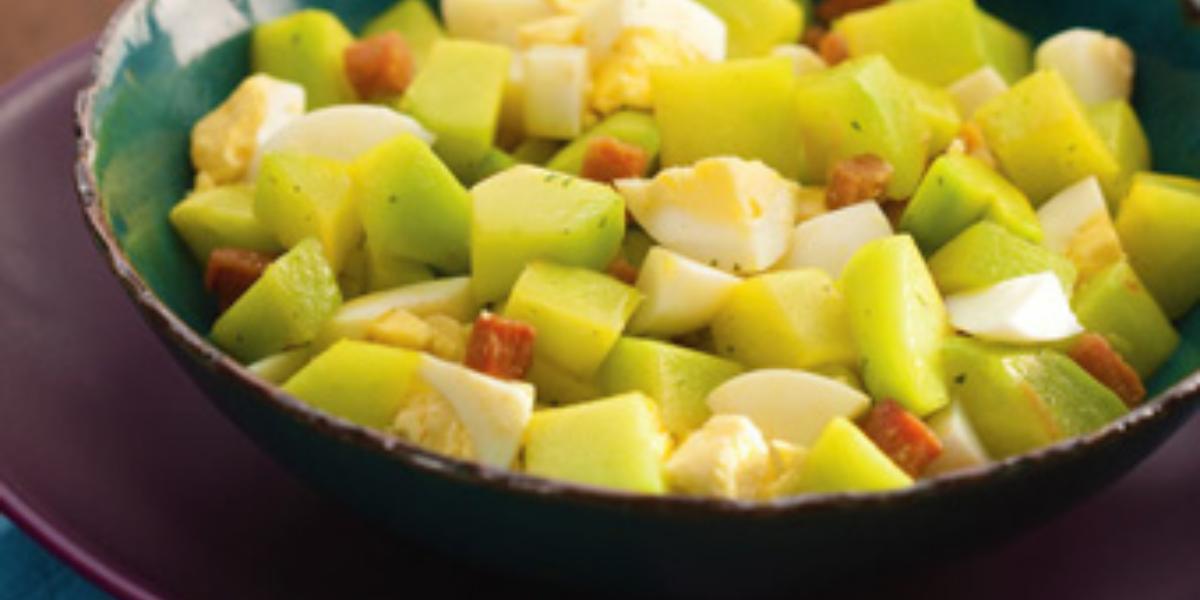 Fotografia em tons de verde e vinho, com saladeira em verde ao centro com chuchu, bacon e ovo cozidos, sobre prato cor vinho e guardanapo azul, sobre bancada marrom.