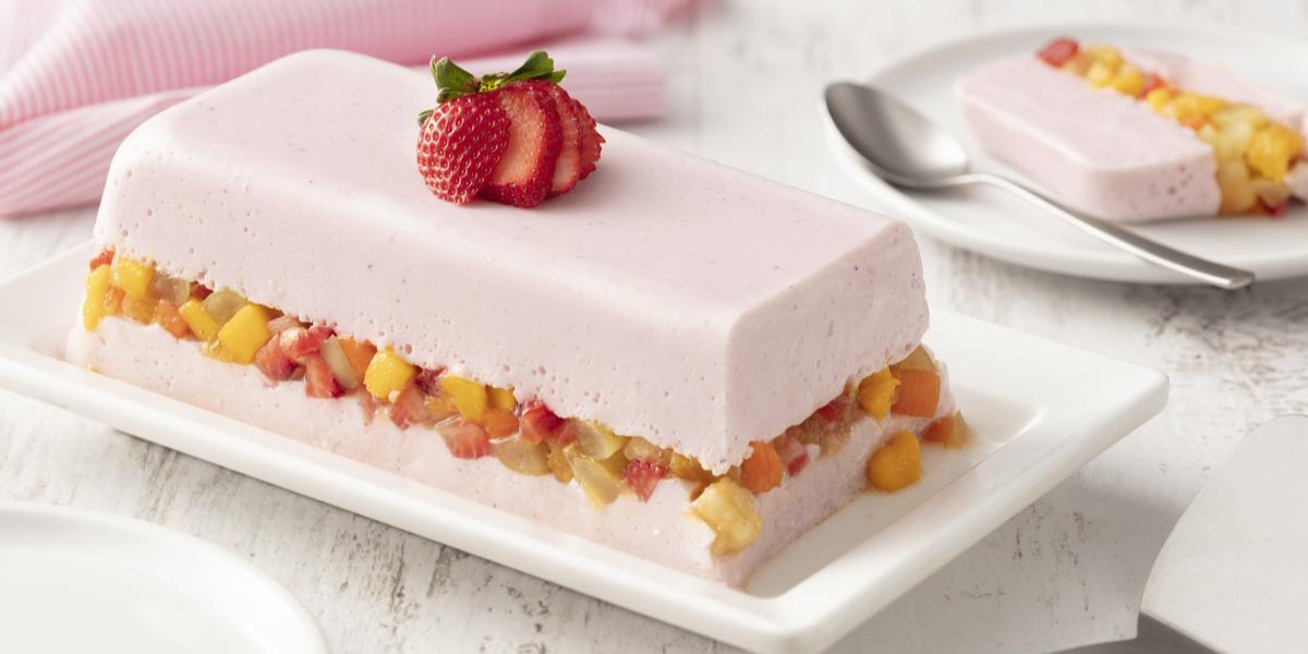 fundo de madeira branca com paninho rosa claro, um prato branco com uma camada de gelatina com iogurte de morango, uma camada de salada de frutas e mais uma camada de gelatina com iogurte de morango.