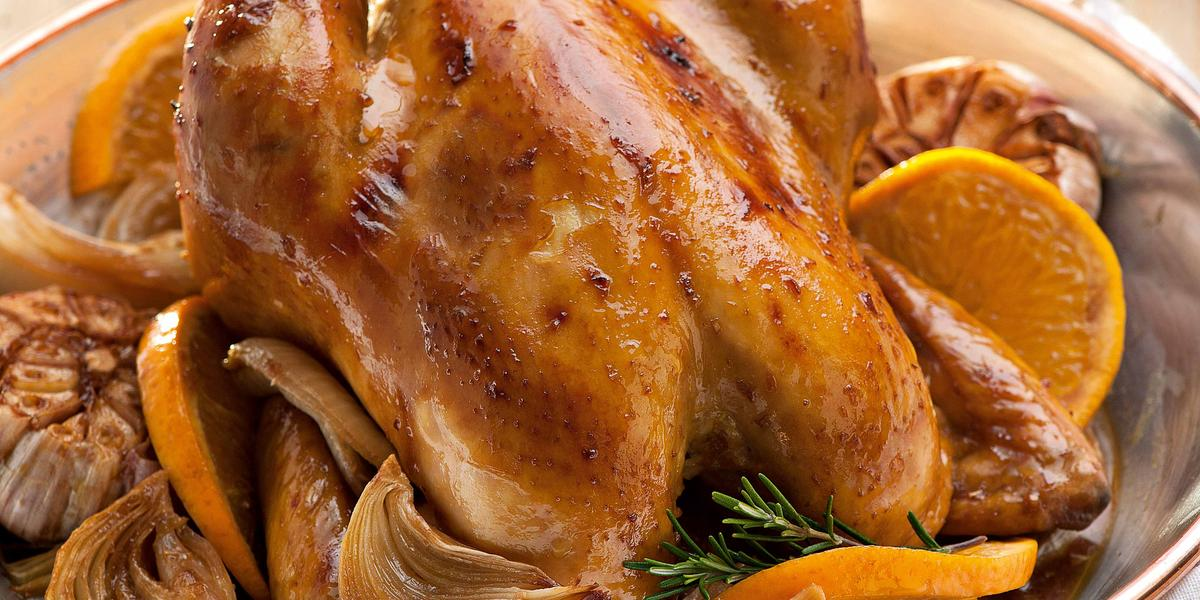 Fotografia em tons de marrom de uma bancada de madeira clara, sobre ela um prato redondo dourado com um frango assado, laranjas e ervas. Ao fundo um prato branco com bordas amarelas.