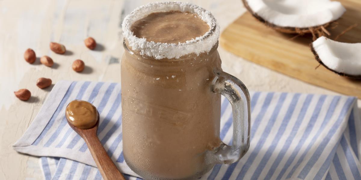 Pano listrado de azul claro e branco, com uma colher de madeira marrom com pasta de amendoim. Uma caneca transparente com o smoothie e borda de coco ralado.