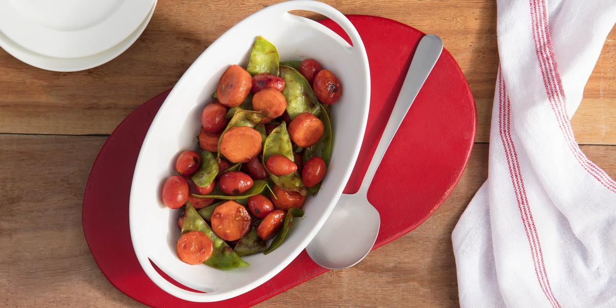 Fotografia em tons de vermelho em uma bancada de madeira, um pano branco com listras vermelhas, um suporte de panela vermelho, um recipiente branco oval com os legumes glaceados dentro.