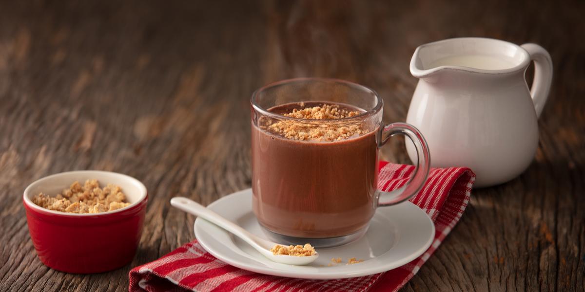 fotografia em tons de marrom, branco e vermelho de uma bancada marrom vista de cima, contém um pano vermelho com um pratinho branco com uma xicara transparente com a bebida de chocolate com paçoca por cima.